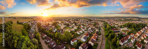Foto Aerial panorama of a small town at sunrise, with magnificent colorful sky and wa