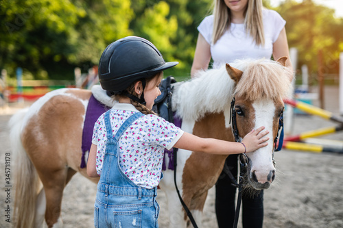 Fototapeta Cute little girl and her older sister enjoying with pony horse outdoors at ranch