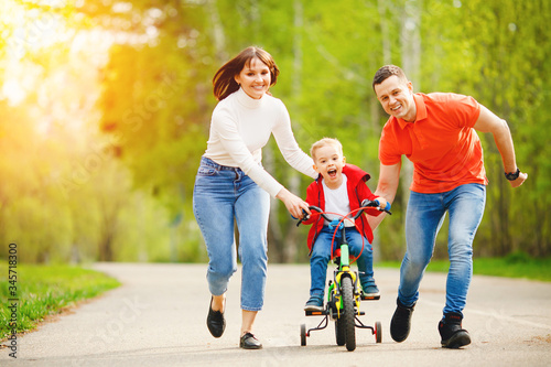Vászonkép Happy father and mom teaching his little kid son to ride bicycle