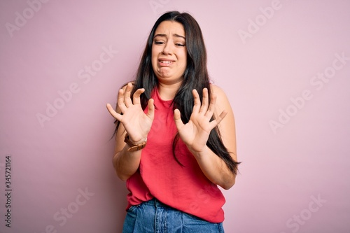 Photo Young brunette woman wearing casual summer shirt over pink isolated background disgusted expression, displeased and fearful doing disgust face because aversion reaction
