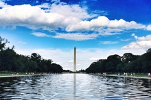 View Of Washington Monument And Trees Against Cloudy Sky