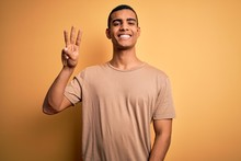 Young Handsome African American Man Wearing Casual T-shirt Standing Over Yellow Background Showing And Pointing Up With Fingers Number Three While Smiling Confident And Happy.