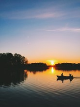 Silhouettes Of Two People In Boat At Sunset