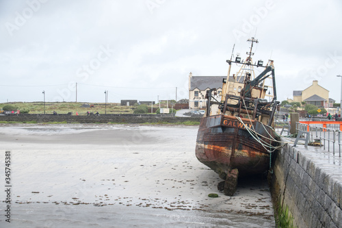 An old Fishing boat grounded in the harbor at Aran Islands, Ireland Canvas Print