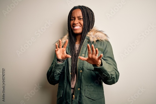 Photo Young african american woman wearing winter parka coat over isolated background disgusted expression, displeased and fearful doing disgust face because aversion reaction