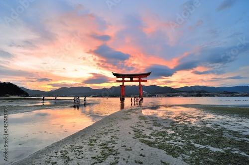 Fotografia Torii Gate In Sea At Itsukushima Shrine Against Sky During Sunset