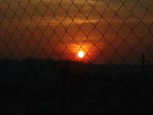 Orange Sky During Sunset Seen From Silhouette Chainlink Fence