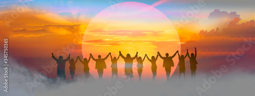 Business people holding and raised arms together on teamwork with sunrise background Obraz na płótnie