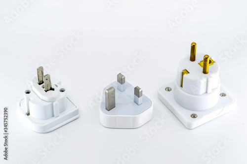 Close up view of three different travel adapter plugs for mains power isolated against a plain white background Wallpaper Mural