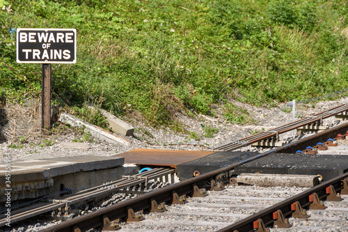 "Photo ""Beware of Trains"" sign on the side of a railway track"