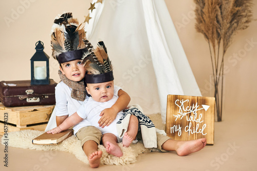 Photo two brothers playing indian in tent on beige background