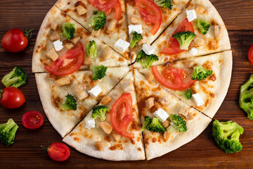 Fototapeta Do pizzerii Pizza with chicken, broccoli and feta cheese on wooden background. Top view