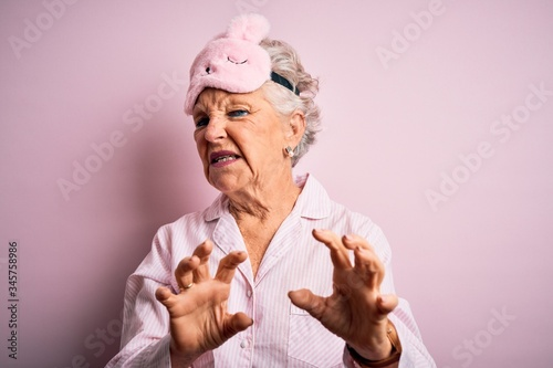 Photo Senior beautiful woman wearing sleep mask and pajama over isolated pink background disgusted expression, displeased and fearful doing disgust face because aversion reaction