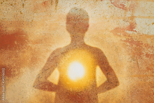 Fotografia Female silhouette radiating light from within a spiritual heart opening
