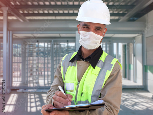 Photo Construction worker in white hardhat and protective mask stands with clipboard o