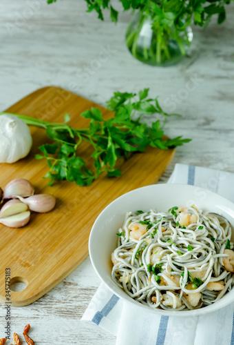 Photo Bol blanco de gulas con gambas, ajos, perejil, guindillas sobre mesa blanca