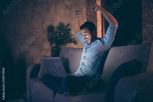 Obraz Profile side view of his he nice attractive lucky cheerful cheery glad brunet guy sitting on divan using laptop rejoicing having fun at modern loft industrial style interior dark room apartment flat - fototapety do salonu
