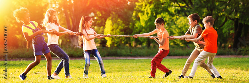 Cute little children playing with rope outdoors on sunny day Poster Mural XXL