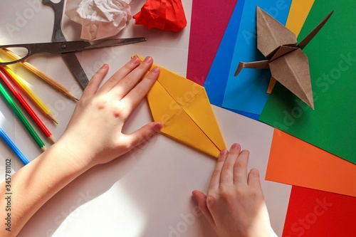 Fototapeta Children's hands doing origami crane from yellow paper on white background with various school supplies