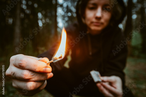 Photo Teenage bully in hood holds burning match in his hand