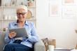 Smiling elderly lady wearing glasses using digital tablet at home
