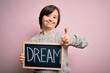 canvas print picture - Young down syndrome woman holding blackboard with dream word as message of happiness happy with big smile doing ok sign, thumb up with fingers, excellent sign