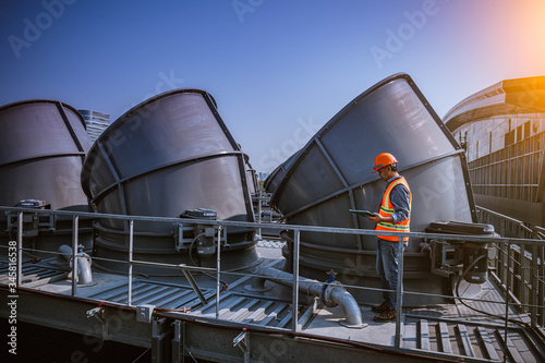 A engineer under checking the industry cooling tower air conditioner is water cooling tower air chiller HVAC of large industrial building to control air system Tapéta, Fotótapéta