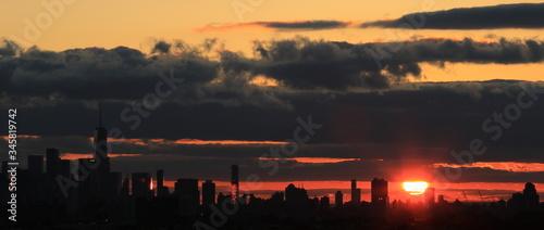 Zachód słońca  nad miastem New York, z groźnymi, ciemnymi chmurami