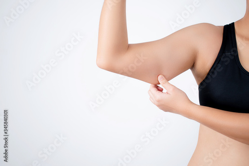 Valokuva Young woman wearing a black workout outfit is pulling under her arm because she has fat under her arm
