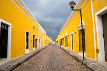 Beautiful Perspective Yellow Street Of The Famous City Of Izamal In Mexico. A Snow-white Carriage Rides Against The Background Of Yellow Houses And Clouds