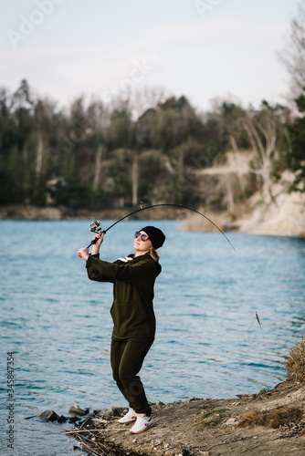 Woman catching a fish on lake or pond with text space Canvas Print