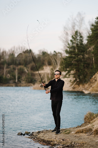 Fisherman with rod throws bait into the water on river bank Canvas Print