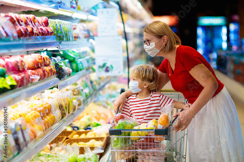 Photo Mother and child buying fruit in supermarket.