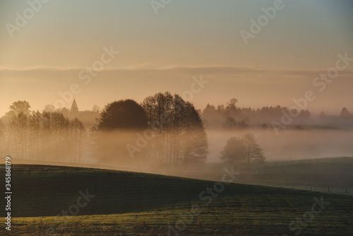 Fototapety, obrazy: morning mist over the field.  Silhouette of the old church.