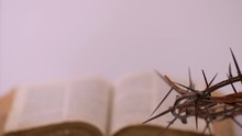 Close Up Of Crown Of Thorns Rotating With Faded Bible In The Background