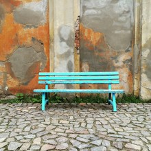 Blue Bench On Street Against Wall