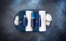 Cosmetic Spa Mockup.Place Your Design. Blue Cosmetic Bottles On Folded Towels In A Basket With Seashells On A Blue Background. Beauty Salon, Table With Creams And Towels, Top View