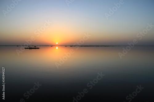Fototapeta Malowniczy wschód słońca na gładkim niebie nad spokojnymi wodami rzeki Niger w afryce obraz