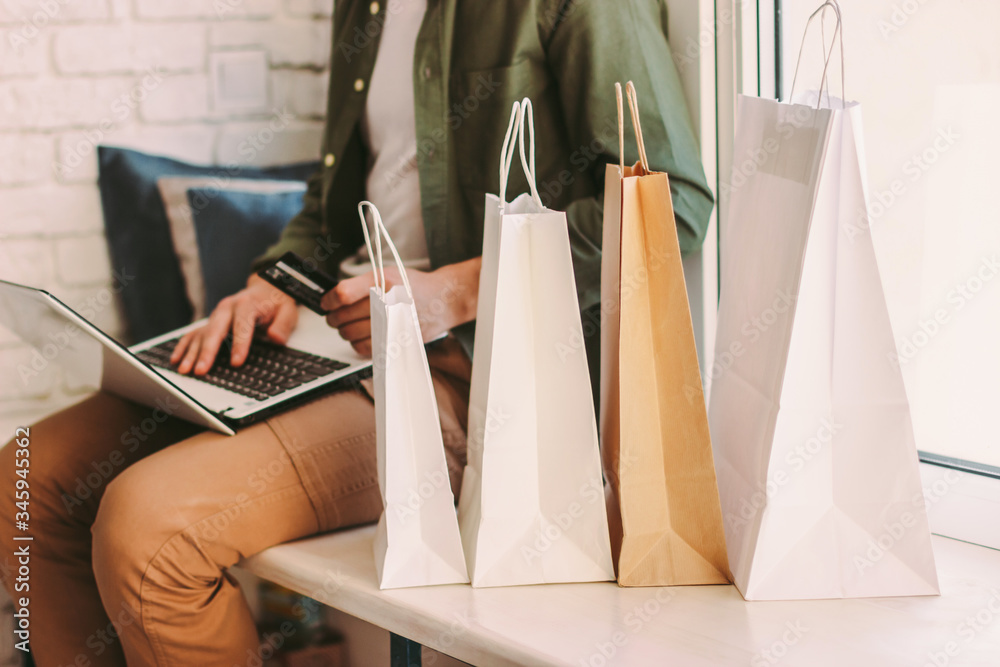 Fototapeta Closeup young hipster man using laptop for online shopping and holding credit card in hand, sitting on windowsill with bags. Stylish man shopper buying at internet store from home. E-commerce, retail