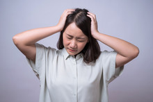 Young Beautiful Asian Woman Suffering From Headache And Stressed Because Pain Migraine, Isolated On Gray Background.