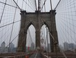 Low Angle View Of Brooklyn Bridge Against Sky During Foggy Weather