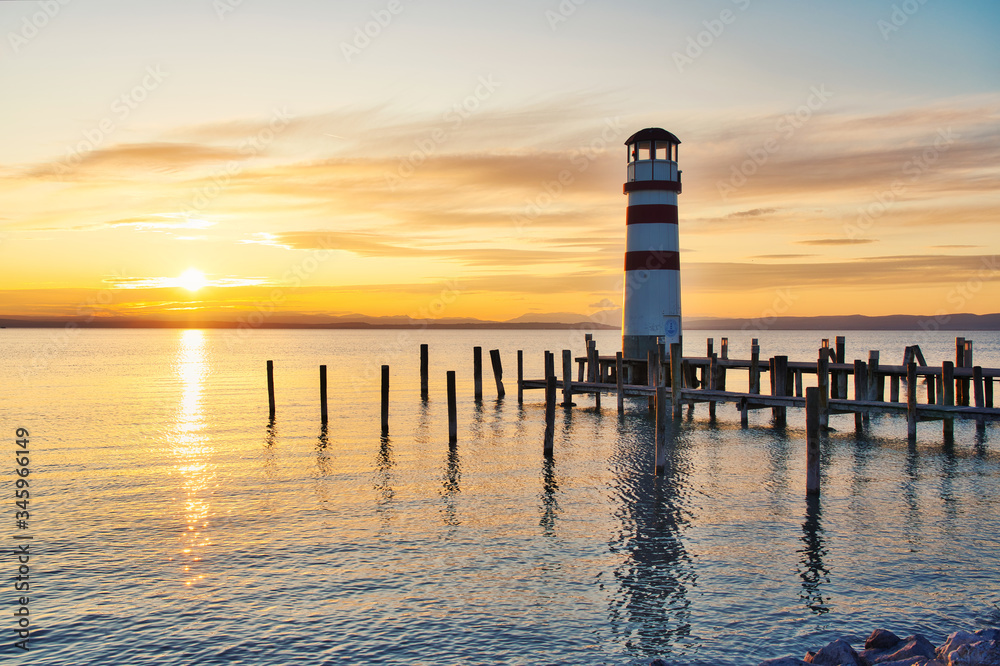 Scenic sunset at idyllic lake Neusiedlersee with old Podersdorf Leuchtturm lighthouse, Burgenland, Austria