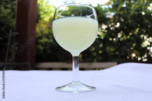 Verre de pastis mélangé avec de l'eau dans un verre rond transparent sur une nap Canvas Print