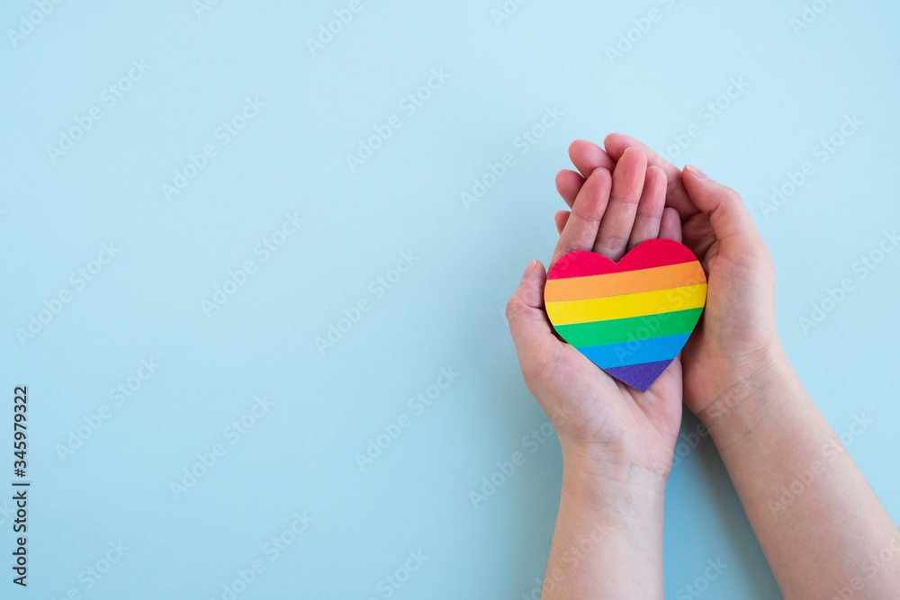 Fototapeta Womans hands hold heart in the colors of rainbow on light blue background. LGBT concept, Pride month. Top view, copy space