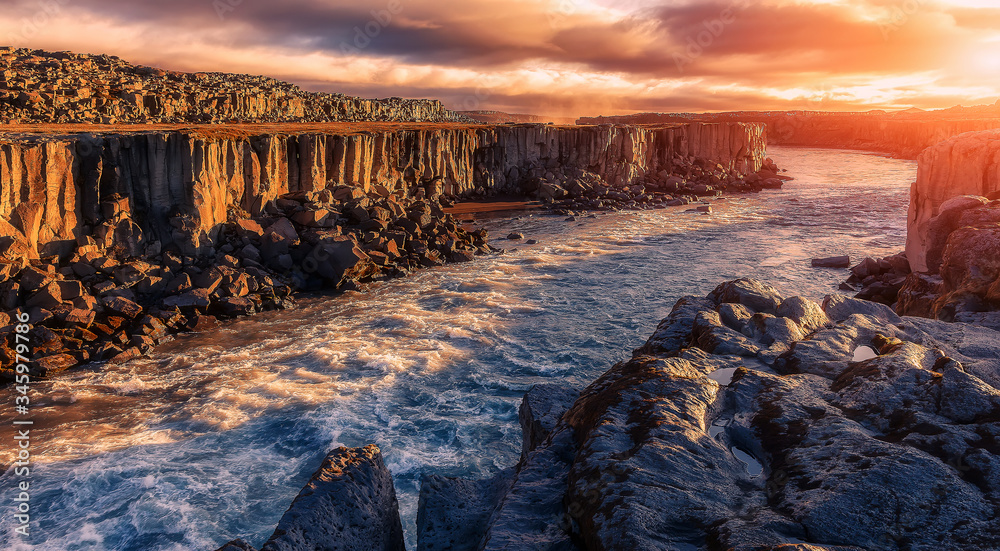 Fototapeta Scenic image nature of Iceland. Amazing tipical Icelandic scenery in summer. The most beautiful conyon with black basalt columns  and river under sunligt in Iceland. Amazing nature landscape.