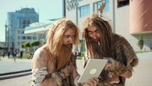 Ancient Wild Homo Sapiens Rejoicing With New Toy Technology Digital Tablet Outdoors. Primitive Timetravelers Of Hunter-gatherers Tribe In Modern Cityscape.