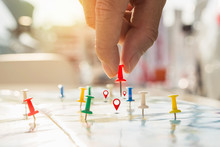 Soft Focus Hand Holding Paper Pin On Blur Perspective Road Map, Red Pin, Point On The Abstract Noname Map. Concept Business Background.