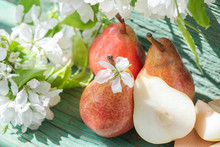 Red Juicy Pears And White Flowers On A Branch On A Green Wooden Table. Vegetarian Food. Beautiful Still Life