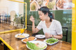 canvas print picture - Asian woman sitting in restaurant eating food with table shield to protect infection from coronavirus covid-19, restaurant and social distancing concept