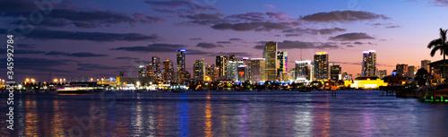 plakat Miami city skyline panorama with urban skyscrapers over sea with reflection. Miami Florida city skyline with night sky.